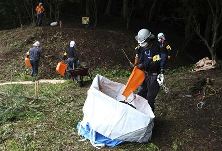 Decontamination workers remove radiated soil and leaves from a forest in Kawauchi village, Fukushima prefecture, July 5, 2013. REUTERS/Sophie Knight