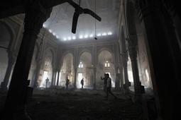 People walk inside the burnt Rabaa Adawiya mosque, the morning after the clearing of a protest which was held around the mosque, in Cairo, August 15, 2013. REUTERS-Mohamed Abd El Ghany