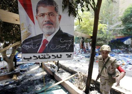 A member of the military police stands beside a poster of deposed Egyptian President Mohamed Mursi that reads: ''No to the coup - The president of all Egyptians'' amid the debris of a cleared protest camp outside the burnt Rabaa Adawiya mosque in Cairo August 15, 2013. REUTERS/Mohamed Abd El Ghany