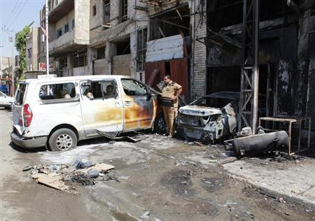 A man stands near vehicles damaged by the impact of a car bomb attack in Baghdad August 15, 2013. REUTERS/Ahmed Saad