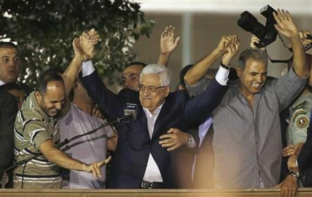 Palestinian President Mahmoud Abbas (C) holds hands with Palestinian prisoners who were released from Israeli prisons during celebrations in the West Bank city of Ramallah early August 14, 2013. REUTERS/Mohamad Torokman
