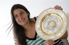 A campeã de Wimbledon Marion Bartoli, da França, ergue seu troféu em entrevista próximo a Paris, França. Com o sonho de uma vida realizado com a conquista do título de Wimbledon, Marion decidiu que não tinha mais nada a buscar no esporte e chocou o mundo do tênis com uma despedida súbita e comovente. 9/07/2013 REUTERS/Christian Hartmann