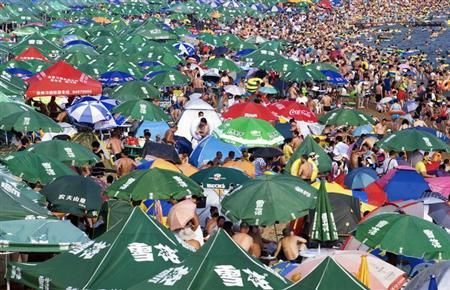 Residents crowd at a beach to escape from the summer heat in Dalian, Liaoning province August 11, 2013. REUTERS/Stringer