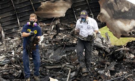 National Transportation Safety Board (NTSB) investigators retrieve the flight voice and data recorders from the wreckage of UPS flight 1354 in this handout photo taken in Birmingham, Alabama August 15, 2013. REUTERS/NTSB/Handout via Reuters