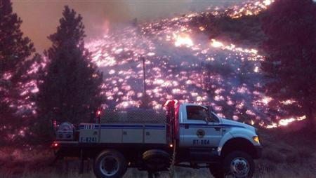 A fire engine patrols the perimeter as the Elk Complex fire burns near the town of Pine, Idaho, in this U.S. Forest Service (USFS) handout picture taken August 13, 2013. REUTERS/USFS/Handout via Reuters