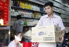 An Abbott Laboratories sales staff carries a carton of powder milk tins out of a shop during a production recall outside Hanoi August 6, 2013. REUTERS/Kham