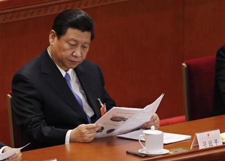 China's Communist Party Chief Xi Jinping reads at the Great Hall of the People during the third plenary session of the National People's Congress (NPC) in Beijing March 10, 2013. REUTERS/Kim Kyung-Hoon