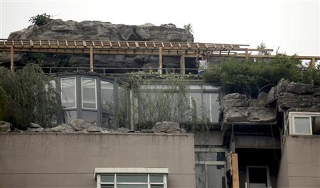 Workers demolish parts of a privately built villa, surrounded by imitation rocks, on the rooftop of a 26-storey residential building in Beijing, August 15, 2013. REUTERS/China Daily