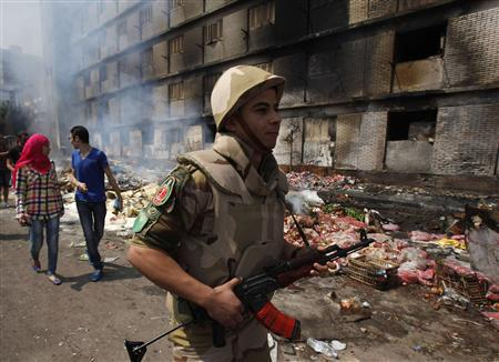 An Egyptian soldier and a couple move near a burnt annex building of Rabaa Adawiya mosque after the clearing of a protest camp around the mosque in Cairo August 15, 2013. REUTERS/Amr Abdallah Dalsh