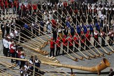 Alphorn players blow their instruments in an attempt to break the world record for the largest ensemble of people playing the alphorn, on the Gornergrat in front of the Matterhorn mountain near Zermatt, 3,089 metres (10,135 feet) above sea level, August 17, 2013. REUTERS/Ruben Sprich