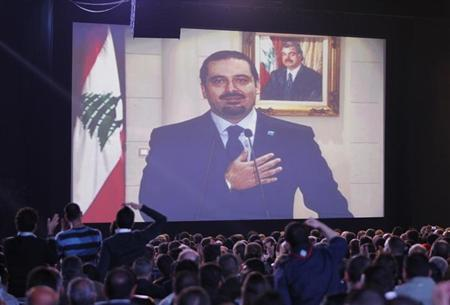 Lebanon's former Prime Minister Saad al-Hariri greets his supporters via a televised screening during a ceremony commemorating the eighth anniversary of the assassination of his father, former Prime Minister Rafik al-Hariri, in Beirut February 14, 2013. REUTERS/Mohamed Azakir