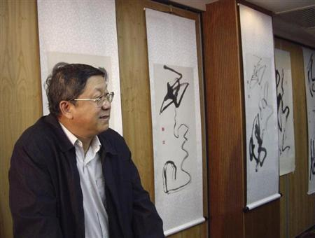 Tang Shuangning, president of Everbright Bank, stands in front of his calligraphy at an exhibition in Beijing May 11, 2008. REUTERS/Simon Rabinovitch/Files