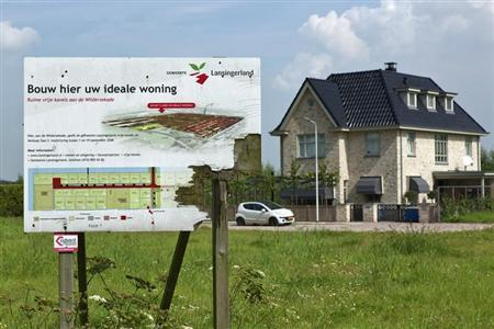 A weathered wooden sign advertising new luxury housing is seen in Lansingerland August 14, 2012. REUTERS/Michael Kooren