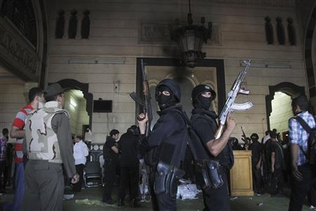 Policemen stand guard inside a room of the al-Fath mosque when supporters of deposed Egyptian President Mohamed Mursi exchanged gunfire with security forces inside the mosque in Cairo August 17, 2013. REUTERS/Muhammad Hamed