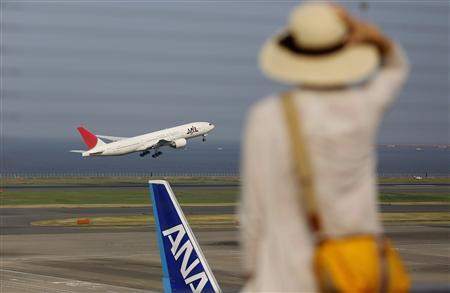 A woman watches a Japan Airlines (JAL) aeroplane (C) taking off behind an All Nippon Airways' (ANA) aeroplane at Haneda airport in Tokyo August 8, 2013. REUTERS/Toru Hanai