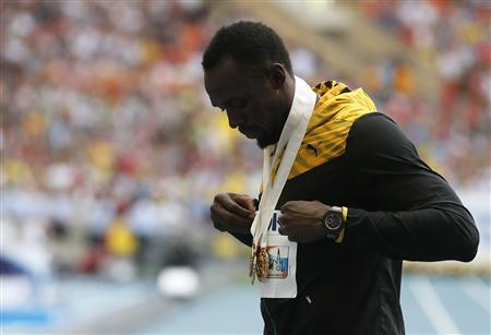 Usain Bolt of Jamaica poses with three gold medals after the victory ceremony for the men's 4x100 metres relay at the IAAF World Athletics Championships at the Luzhniki stadium in Moscow August 18, 2013. REUTERS/Lucy Nicholson