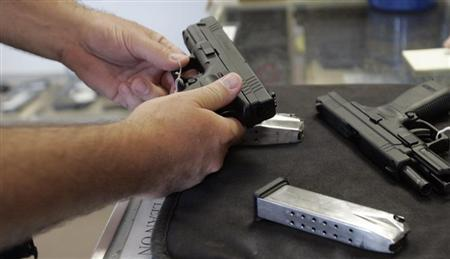 A customer inspects a 9mm handgun at Rink's Gun and Sport in the Chicago, suburb of Lockport, Illinois in this June 26, 2008 file photograph. REUTERS/Frank Polich/Files