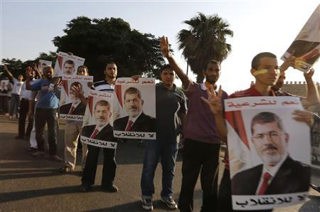 Supporters of deposed Egyptian President Mohamed Mursi hold up posters of him during a protest along Zahara street in Cairo August 18, 2013. REUTERS-Louafi Larbi