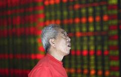 An investor looks at an electronic board showing stock information at a brokerage house in Shenyang, Liaoning province August 16, 2013. REUTERS/Stringer
