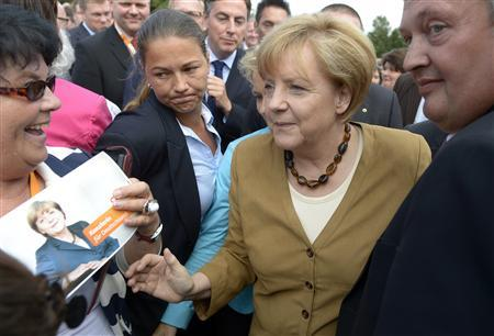 German Chancellor Angela Merkel (CDU) (C) is welcomed by supporters as she arrives at an election campaign in Cloppenburg, August 17, 2013. REUTERS/Fabian Bimmer