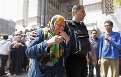 """Полицейский успокаивает плачущую мать сторонника свергнутого Мохамеда Мурси в мечети Аль-Фатх на каирской площади Рамзес 17 августа 2013 года. Борющееся за политическое выживание движение египетских """"Братьев-мусульман"""" обвинило полицейских в убийстве 36 арестованных сторонников. Полиция сообщила, что они погибли при попытке побега, и в ответ обвинила исламистов в расстреле двух десятков полицейских из засады в понедельник. REUTERS/Mohamed Abd El Ghany"""