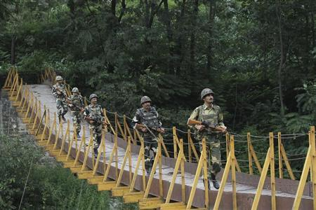 Border Security Force (BSF) soldiers patrol over a footbridge built over a stream near the Line of Control (LoC), a ceasefire line dividing Kashmir between India and Pakistan, at Sabjiyan sector of Poonch district, August 8, 2013. REUTERS/Mukesh Gupta