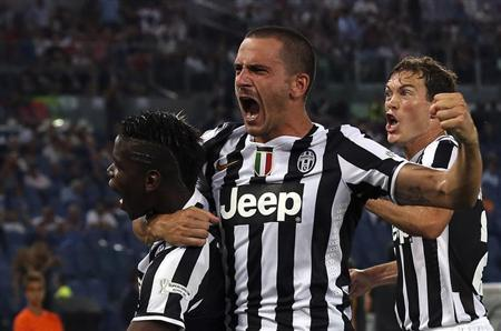 Juventus' Paul Labile Pogba (L) celebrates with his teammates Leonardo Bonucci (C) and Stephan Lichtsteiner (R) after scoring against Lazio during their Italian Super Cup at the Olympic stadium in Rome August 18, 2013. REUTERS/Alessandro Bianchi