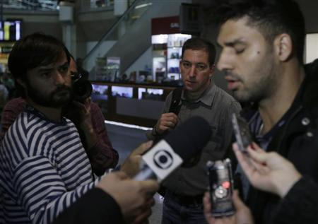 U.S. journalist Glenn Greenwald (C) looks on as his partner David Miranda (R) talks with the media after arriving at Rio de Janeiro's International Airport August 19, 2013. REUTERS/Ricardo Moraes