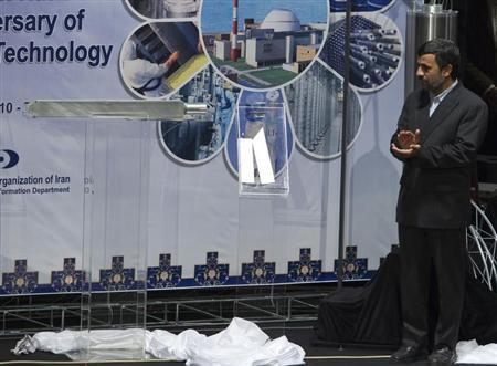 Iranian President Mahmoud Ahmadinejad claps as he looks at an object representing nuclear fuel which will be used in Tehran's research reactor during a ceremony to mark the Fourth National Anniversary of Nuclear Technology, in Tehran April 9, 2010. REUTERS/Morteza Nikoubazl