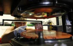 Employee Eva Sipova removes a new record from the press machine as part of the creation process for vinyl records at the GZ Media factory in Lodenice August 1, 2013. REUTERS/Petr Josek