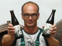 "Austrian brewer Peter Krammer displays two bottles of his ""Neuhauser Herrschafts Pier"" in the family-owned Hofstetten brewery in the Upper Austrian town of Saint Martin August 13, 2013. REUTERS/Heinz-Peter Bader"