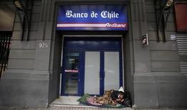 Un indigente duerme a las puertas de unas oficinas del Banco de Chile en Santiago. Agosto, 2014. REUTERS/Iván Alvarado. La economía chilena creció en el segundo trimestre a su menor ritmo en dos años debido a una expansión más moderada de la demanda interna, lo que daría más argumentos al Banco Central para un eventual relajamiento de la política monetaria en la segunda mitad del año.
