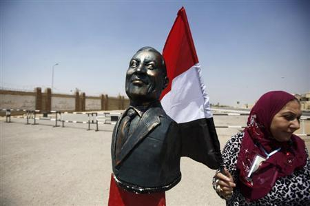 A supporter of Egypt's former President Hosni Mubarak holding an Egyptian flag stands next to a bust of Mubarak outside a police academy before Mubarak's trial in Cairo July 6, 2013. REUTERS/Amr Abdallah Dalsh/Files