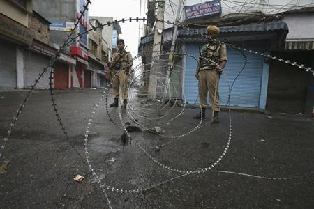 Policemen stand guard at a street during a curfew following riots, in Jammu August 12, 2013. REUTERS/Mukesh Gupta