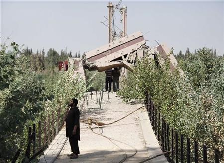 A fighter from the Islamist Syrian rebel group Jabhat al-Nusra stands on the historical Deir al-Zor Suspension Bridge, damaged by what activists said was by forces loyal to Syria's President Bashar al-Assad August 17, 2013. REUTERS/Khalil Ashawi