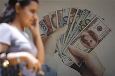 El euro subió a un máximo de dos semanas contra el yen y avanzó ante el dólar el lunes, impulsado por comentarios del Bundesbank que sugerían que la promesa de bajas tasas de interés del Banco Central Europeo hecha el mes pasado no está escrita en piedra. En la foto de archivo, una mujer pasa delante de un cartel en un banco en Mumbai, India. Agosto 19, 2013. REUTERS/Danish Siddiqui