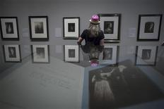 A woman looks at photographs displayed during an exhibition of Julia Margaret Cameron's photographs at the Metropolitan Museum of Art in New York August 19, 2013. REUTERS/Lucas Jackson