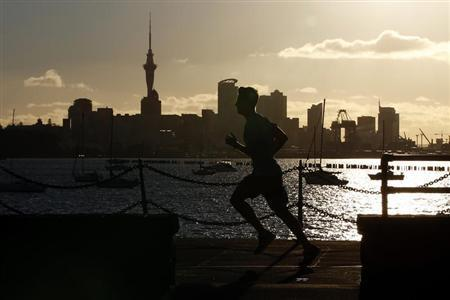A jogger runs along the seawall in Auckland September 26, 2011, with the city skyline in the background. REUTERS/Stefan Wermuth