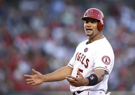 Los Angeles Angels' Albert Pujols gestures towards the New York Yankees dugout after hitting a single during the first inning of their MLB American League baseball game in Anaheim, California June 14, 2013. REUTERS/Danny Moloshok