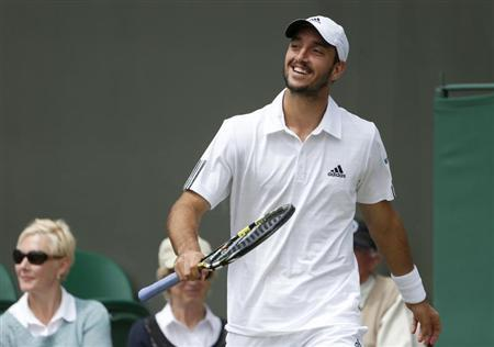 Viktor Troicki of Serbia reacts after slipping in his men's singles tennis match against Mikhail Youzhny of Russia at the Wimbledon Tennis Championships, in London June 29, 2013. REUTERS/Suzanne Plunkett