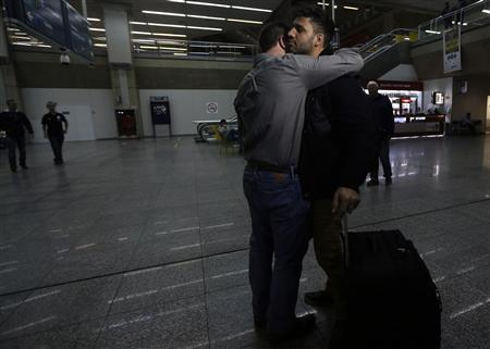U.S. journalist Glenn Greenwald (front L) embraces his partner David Miranda upon his arrival at Rio de Janeiro's International Airport August 19, 2013. REUTERS/Ricardo Moraes