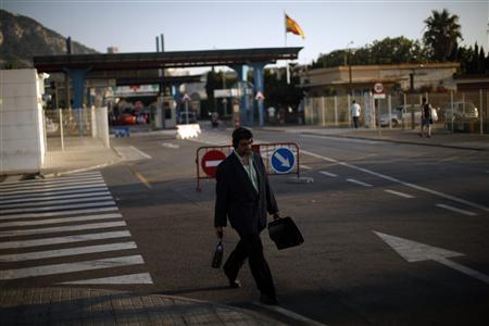 A man leaves the British territory of Gibraltar at its border with Spain, in la Linea de la Concepcion, southern Spain August 19, 2013. REUTERS/Jon Nazca