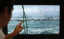 """Профессор Блэр Торнтон в Токийском институте индустриальных исследований указывает на видеосъемку АЭС """"Фукусима"""" 8 августа 2013 года. Сотни тонн воды с высоким уровнем радиации утекли из хранилища на повреждённой АЭС Фукусима в Японии, что стало самой серьёзной неудачей в ликвидации последствий худшего со времён Чернобыля инцидента в ядерной энергетике. REUTERS/Toru Hanai"""