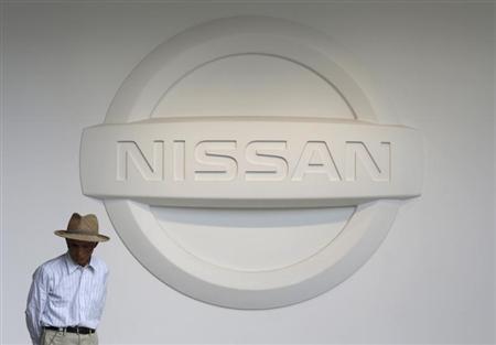 A man walks past next to the logo of Nissan Motor Co. at the company's showroom in Yokohama, south of Tokyo May 10, 2013. REUTERS/Toru Hanai