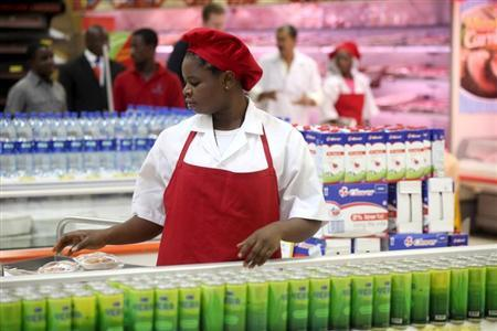A shop assistant arranges products at the South African firm Shoprite's main store in Nigeria's commercial capital Lagos April 29, 2010. REUTERS/Akintunde Akinleye