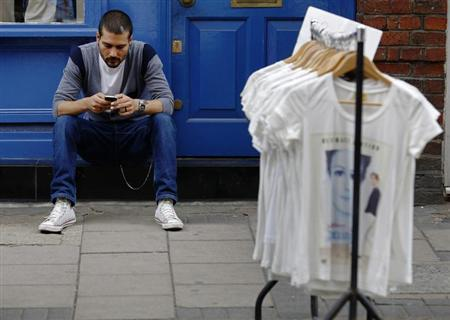 A man uses his mobile phone next to a rail of clothes for sale in central London August 10, 2013. A deal to take BlackBerry Ltd private could make sense from a financial standpoint, say private equity executives, though any such move won't by itself make the smartphone company more competitive. REUTERS/Luke MacGregor