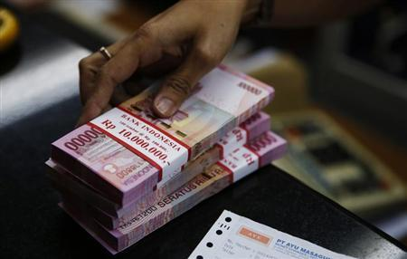 A money changer holds stacks of Indonesian rupiah notes in Jakarta August 20, 2013. REUTERS/Beawiharta
