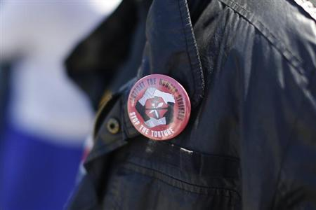 A man wears a pin in support of inmates who are participating in a state-wide prisoner hunger strike demanding an end to indefinite solitary confinement in California's prison system outside San Quentin State Prison in San Quentin, California August 3, 2013. REUTERS/Stephen Lam