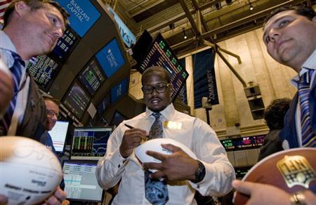 NFL draft prospect Von Miller signs a football for traders on the New York Stock Exchange floor before he rings the closing bell in New York April 27, 2011. REUTERS/Mark Dye