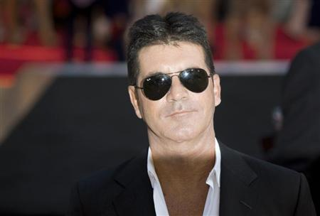 Television mogul Simon Cowell poses for photographers as he arrives for the film ''One Direction: This is Us'', in London August 20, 2013. REUTERS/Neil Hall